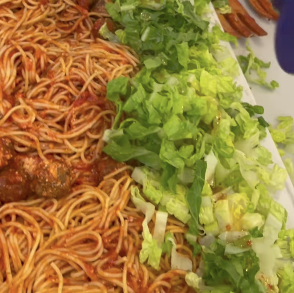 Salad added to pile of spaghetti