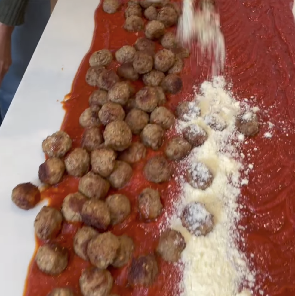 Parmesan cheese getting dumped on meatballs and sauce