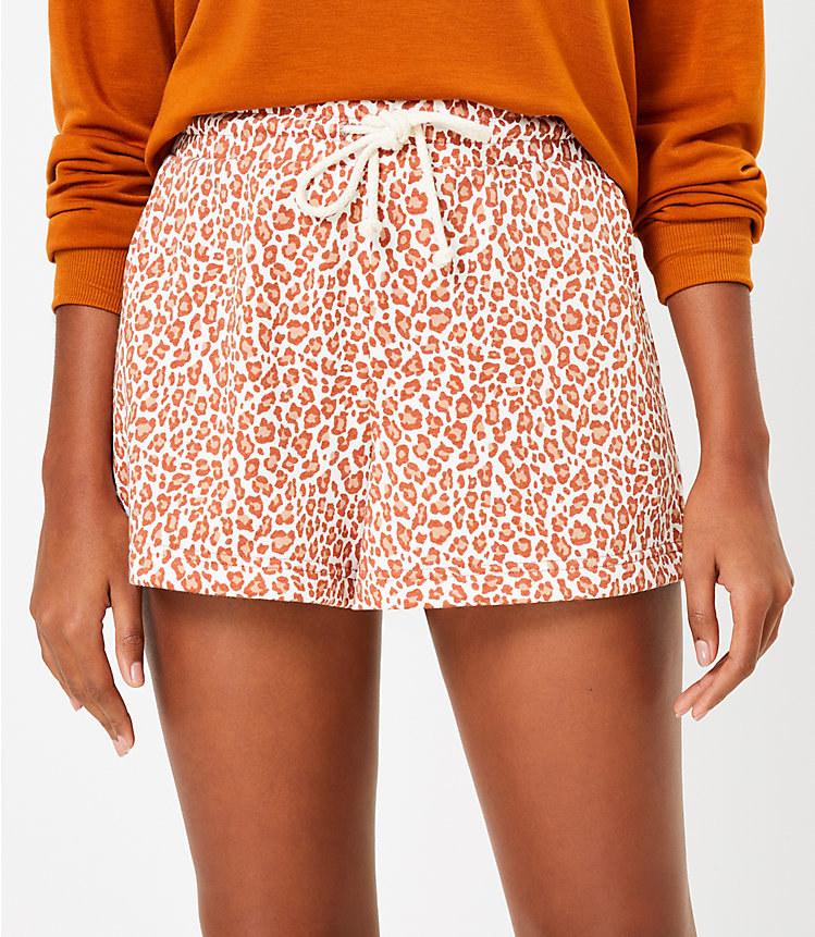 model wearing the white and orangish-brown shorts