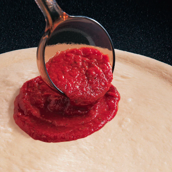 sauce being spread onto pizza dough