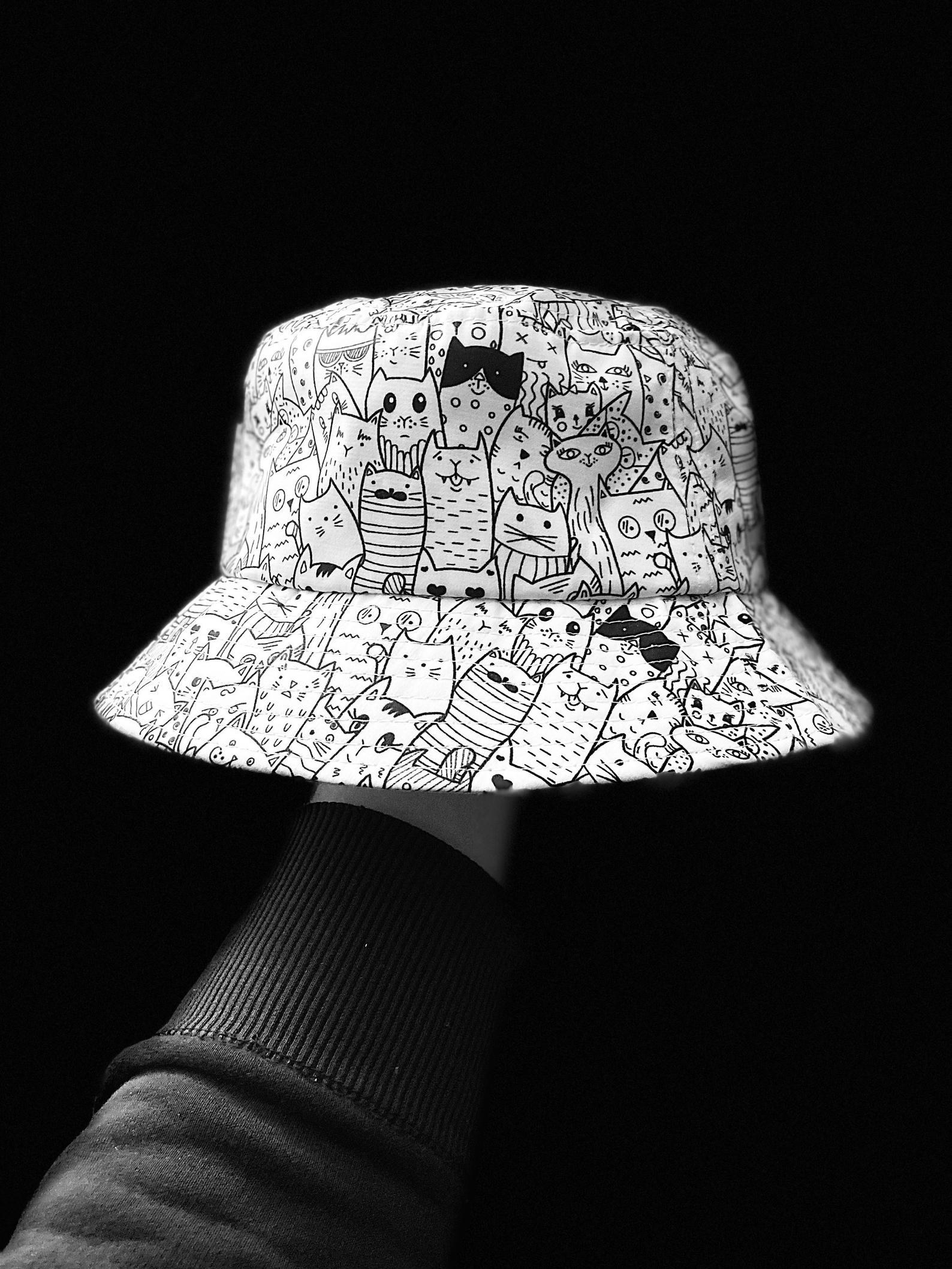 a hand holds up the doodle cat bucket hat