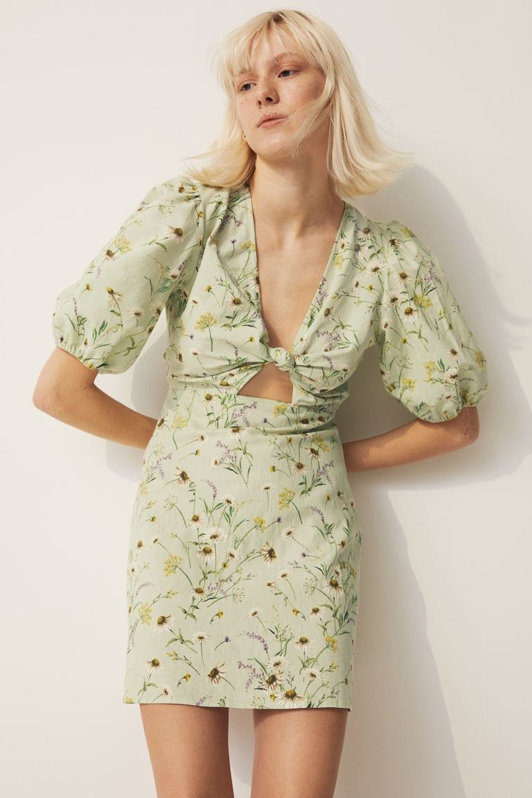 model wearing mini dress with floral pattern on it, puffy sleeves, a V-neck, and a keyhole under the chest