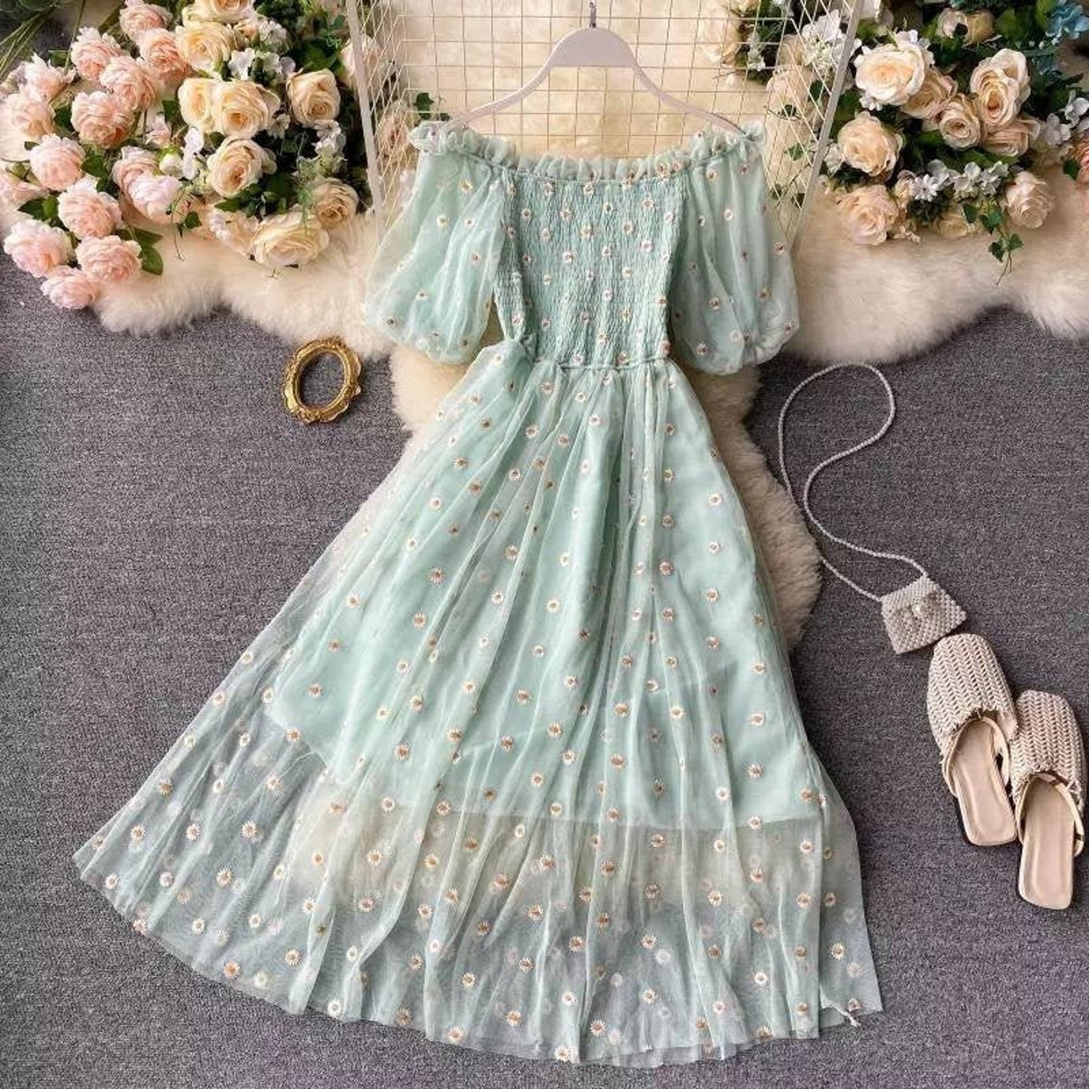 off the shoulder light green dress with puffy sleeves and a sheer overlay with embroidered flowers on it