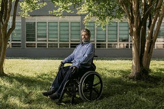 Francis Brauner sits in his wheelchair in front of an institutional building