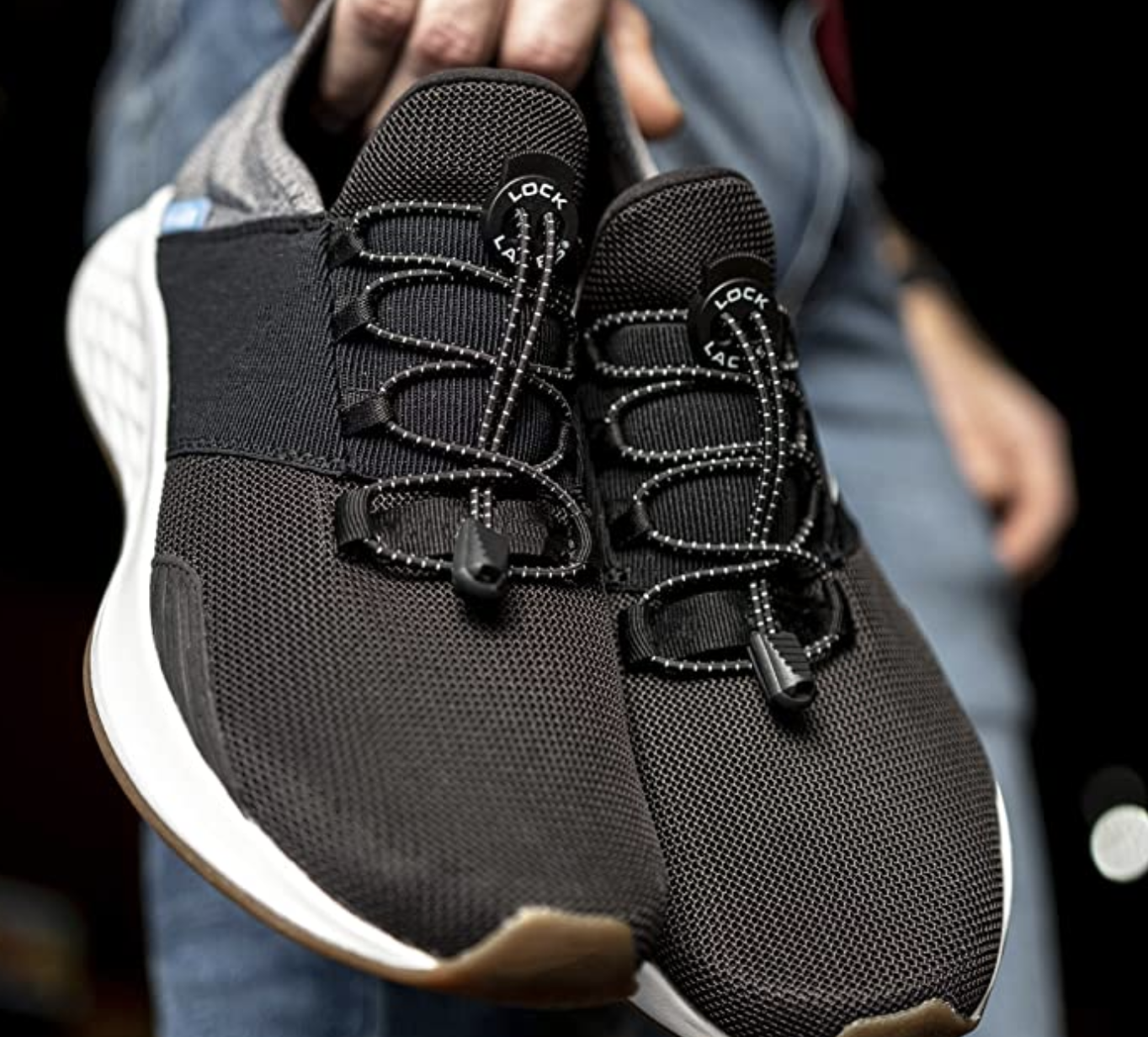 """A pair of sneakers with black bungee-like """"lock laces"""" in the shoe lace straps"""