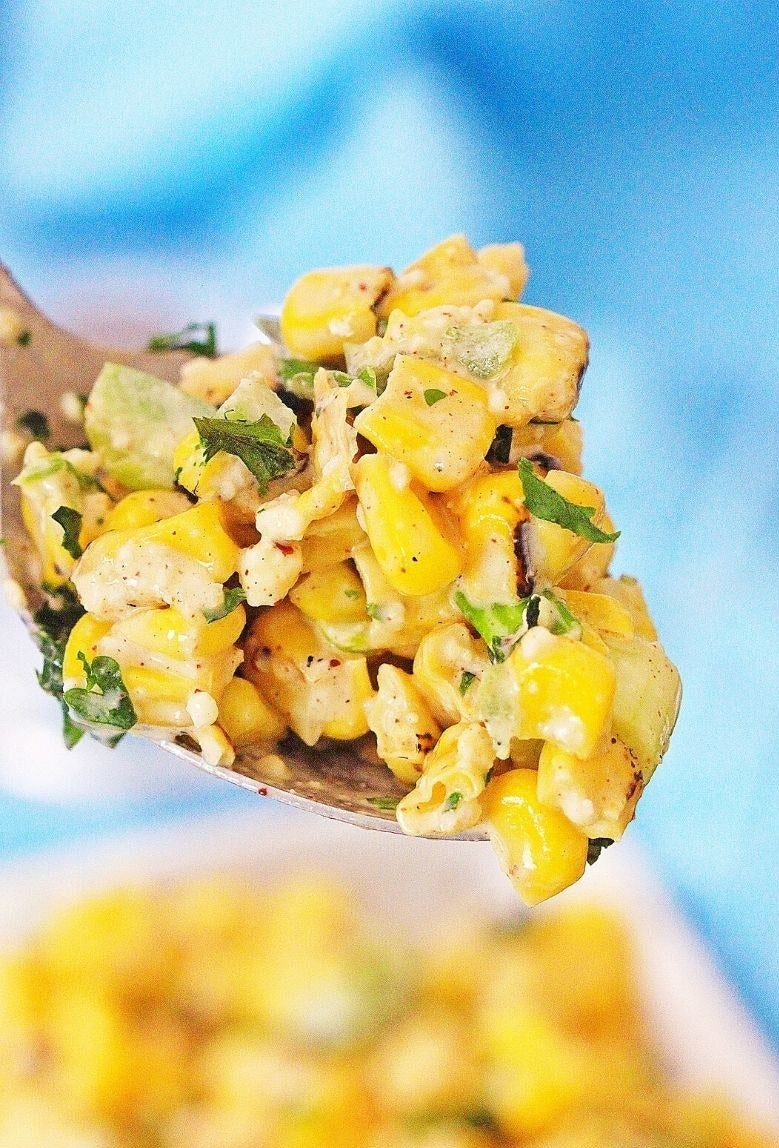A wooden spoon taking a scoop of Mexican street corn