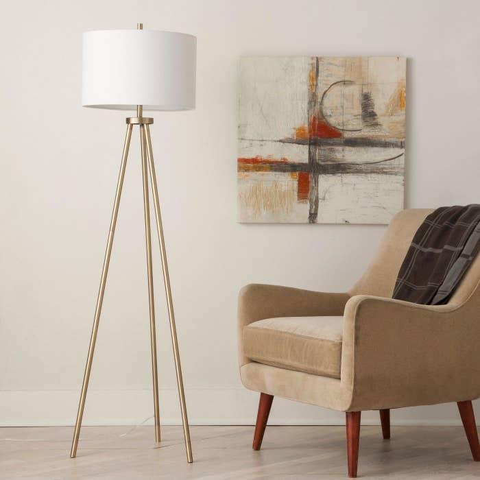 A gold tripod lamp in a home
