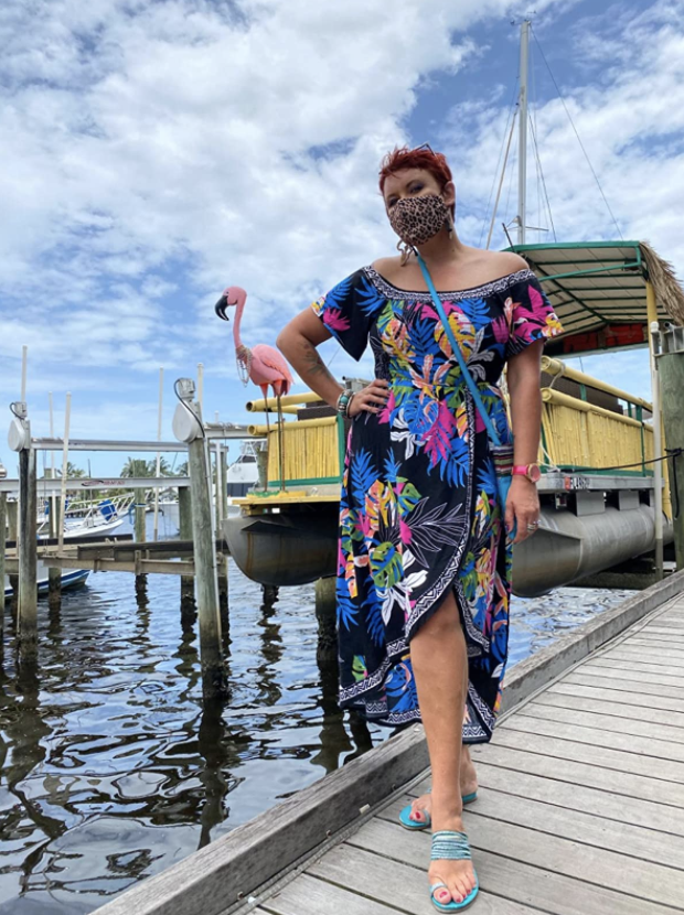 reviewer wearing off the shoulder floral short sleeve dress with wrap skirt on a dock by boats