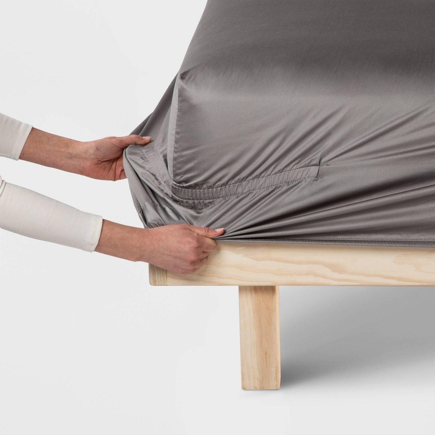 a model putting a fitted sheet on a mattress