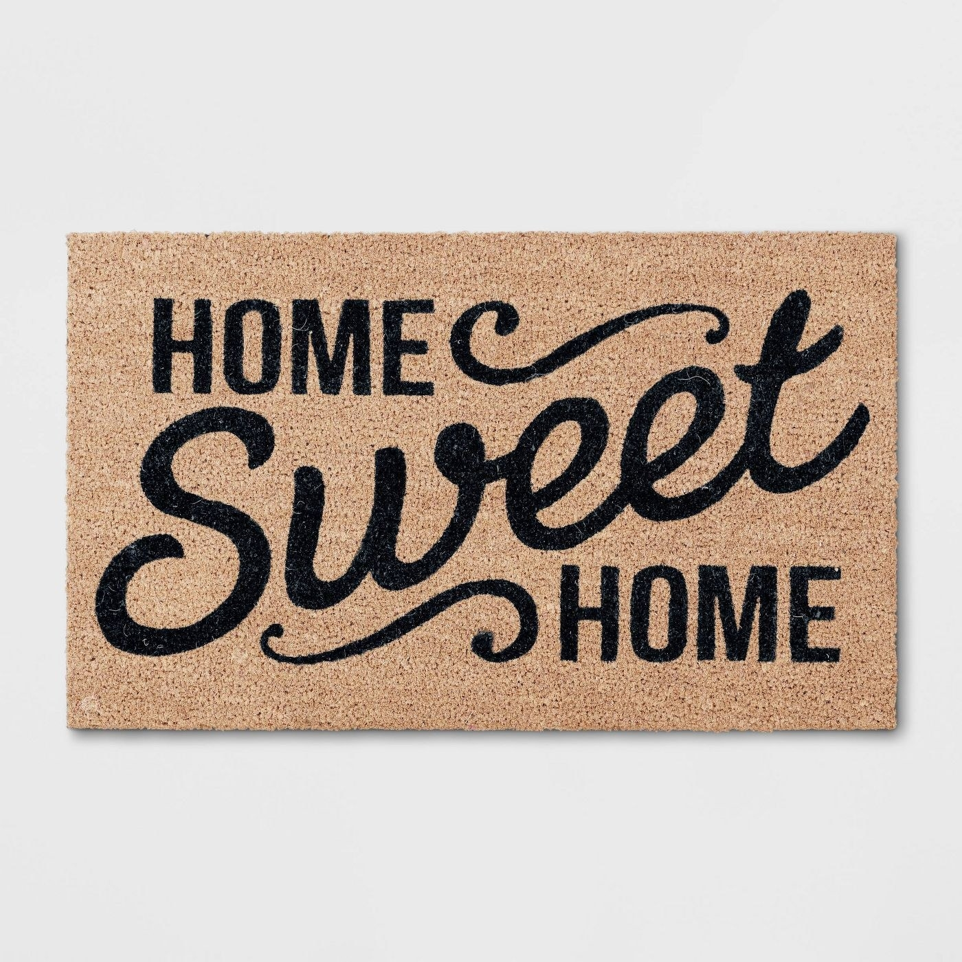 """""""Home sweet home"""" in black font on a brown mat"""