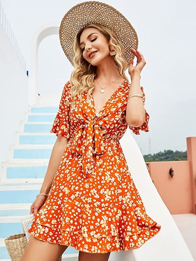 model in a short A-line floral dress with a V-neck that ties low at the bust