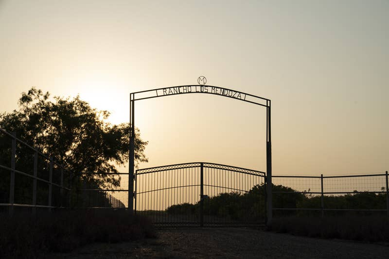 A large iron fence with a sign that reads Rancho Los Mendoza