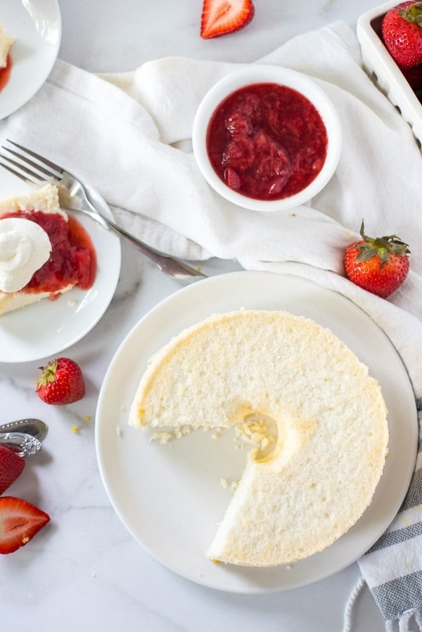 An angel food cake with fresh strawberry topping.
