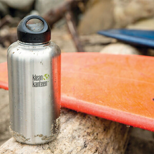 the klean kanteen stainless steel water bottle on a log next to a surf board