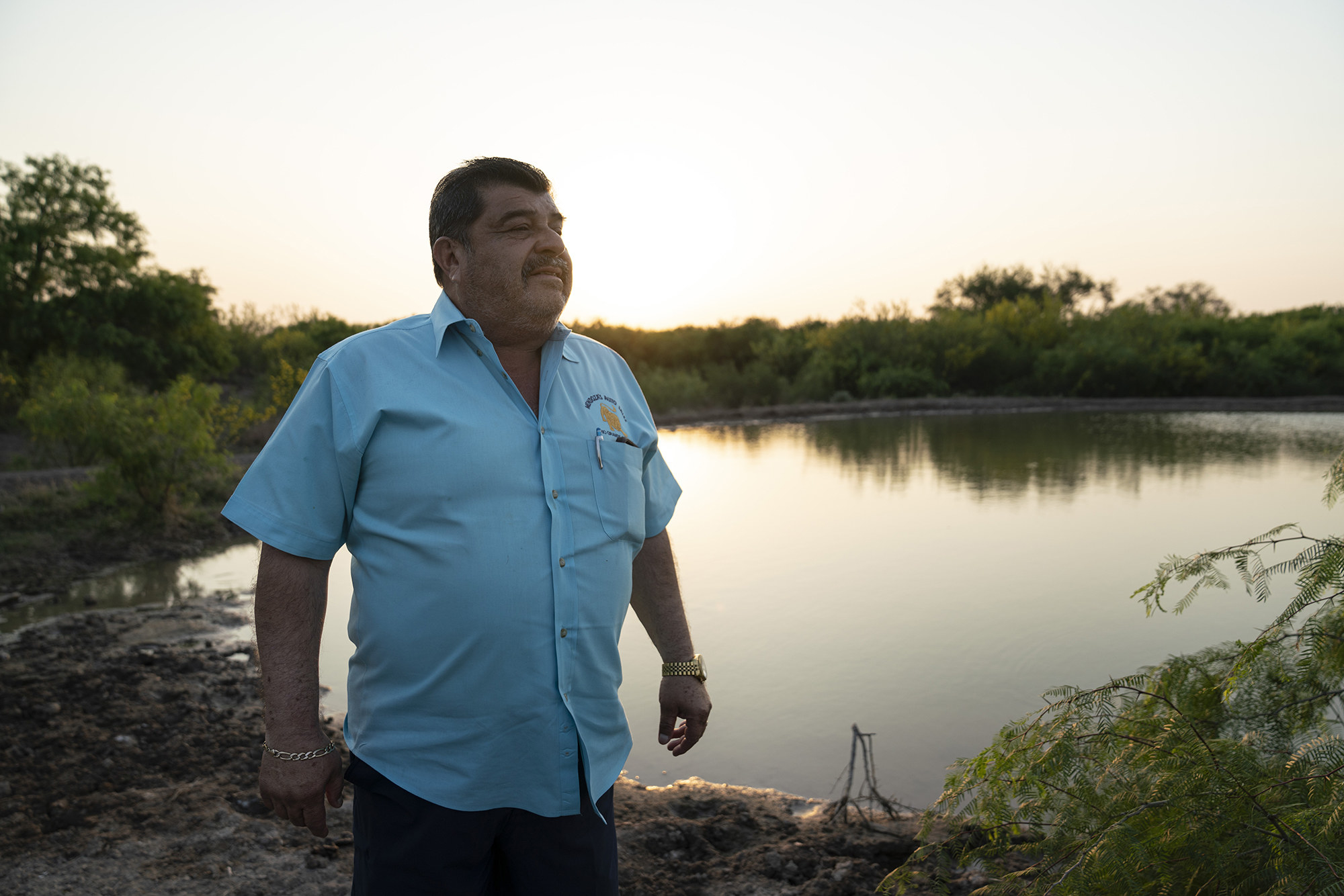 Ociel Mendoza in front of a shallow pond on his ranch at sunset