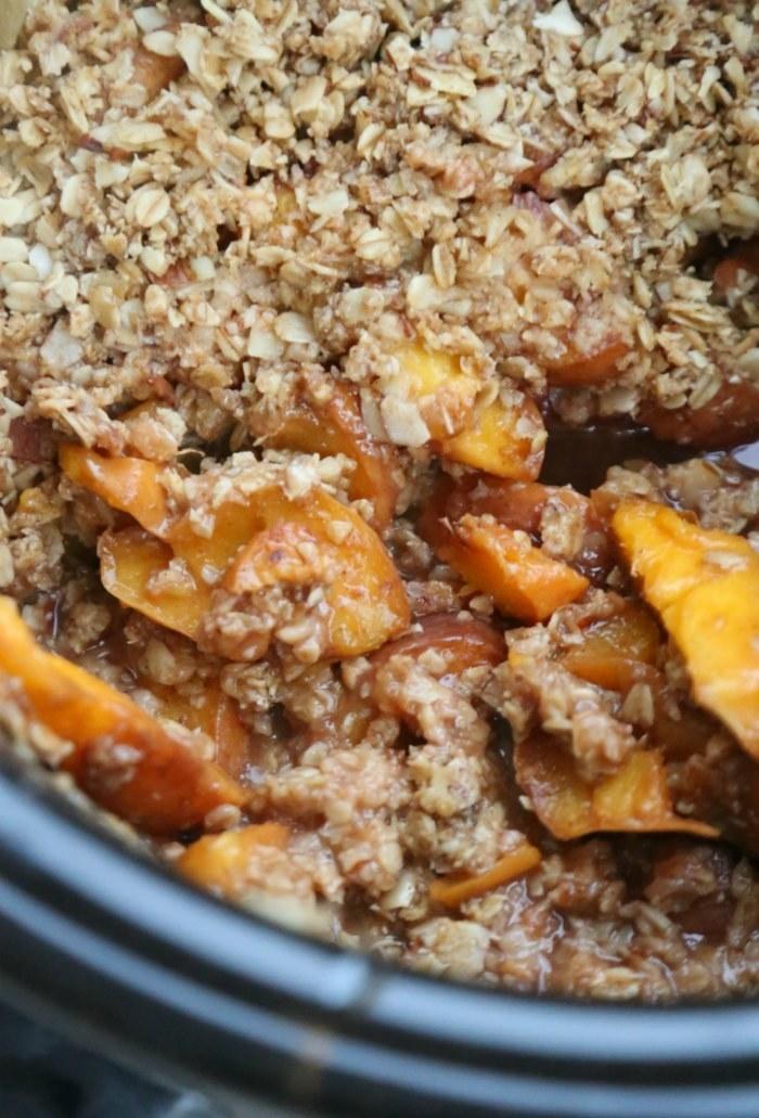 A slow cooker full of peach crisp.