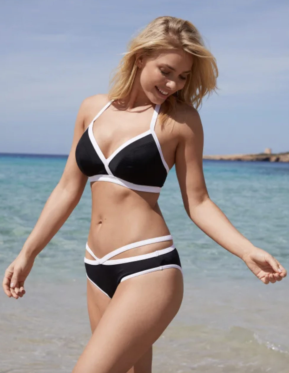 model wearing black bikini with white trim