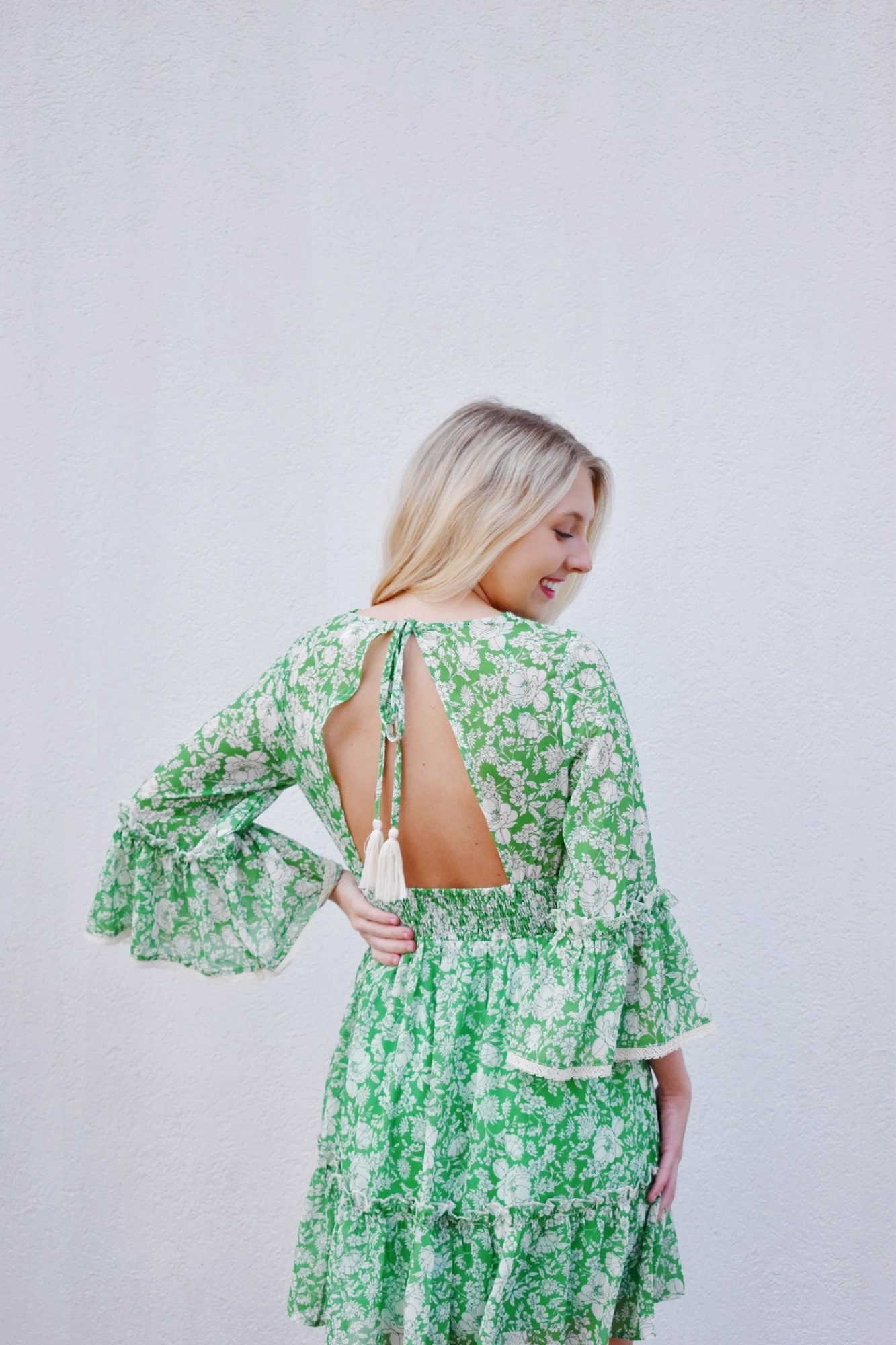 model wearing bell sleeve dress with cutout in the back