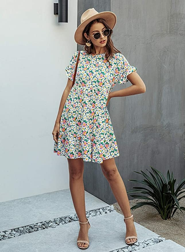 model wearing short sleeve floral dress with strappy sandals