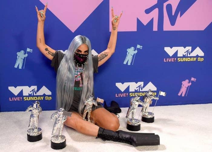 Lady Gaga posing with her Moonmen awards at the VMAs