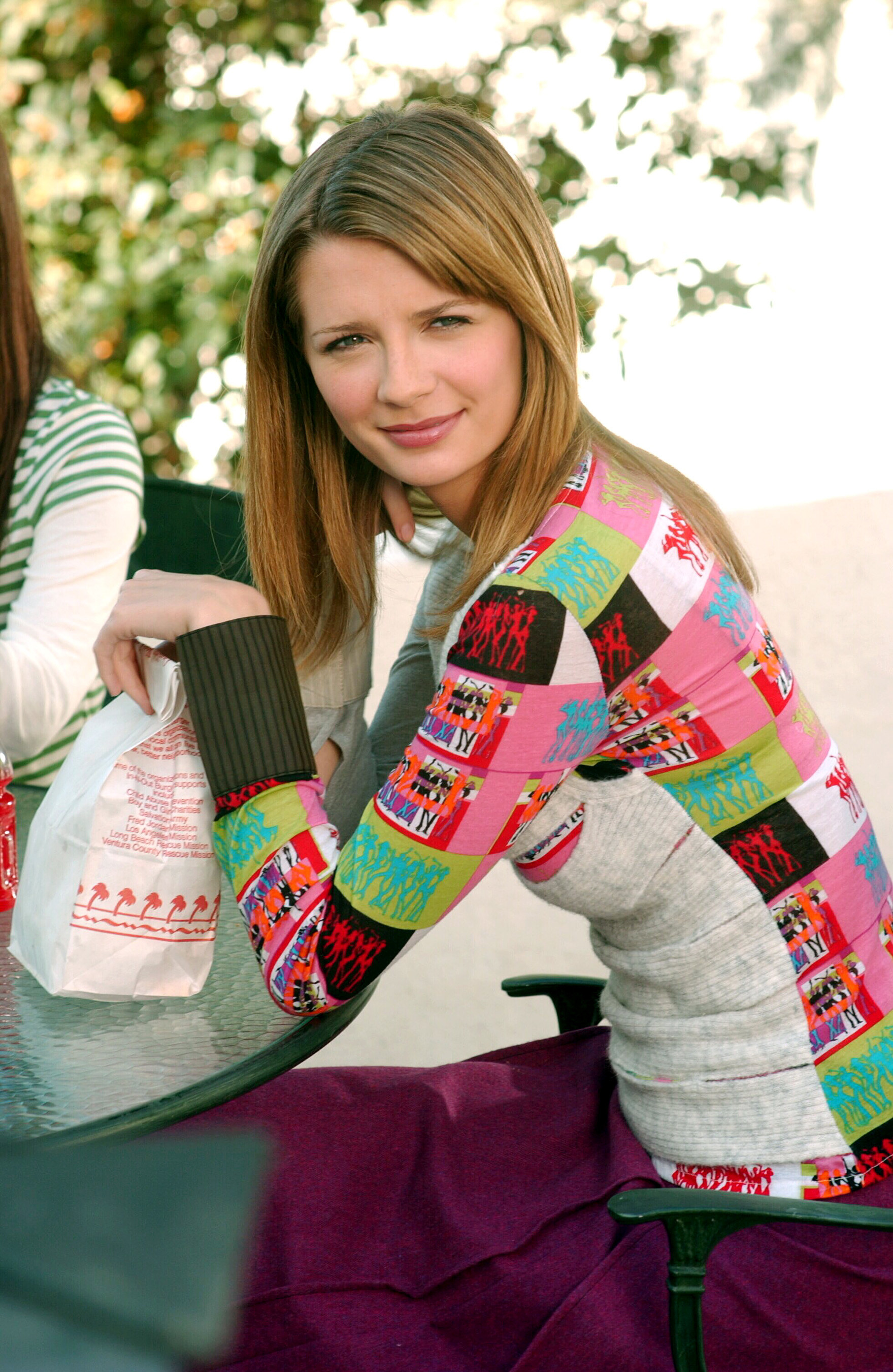 Long-sleeve shirt with thick sweater wrist cuffs, a square patchwork pattern on the back, a solid front and other sleeve, and a dark low-waisted long skirt