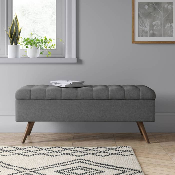 grey upholstered tufted storage bench with books on top