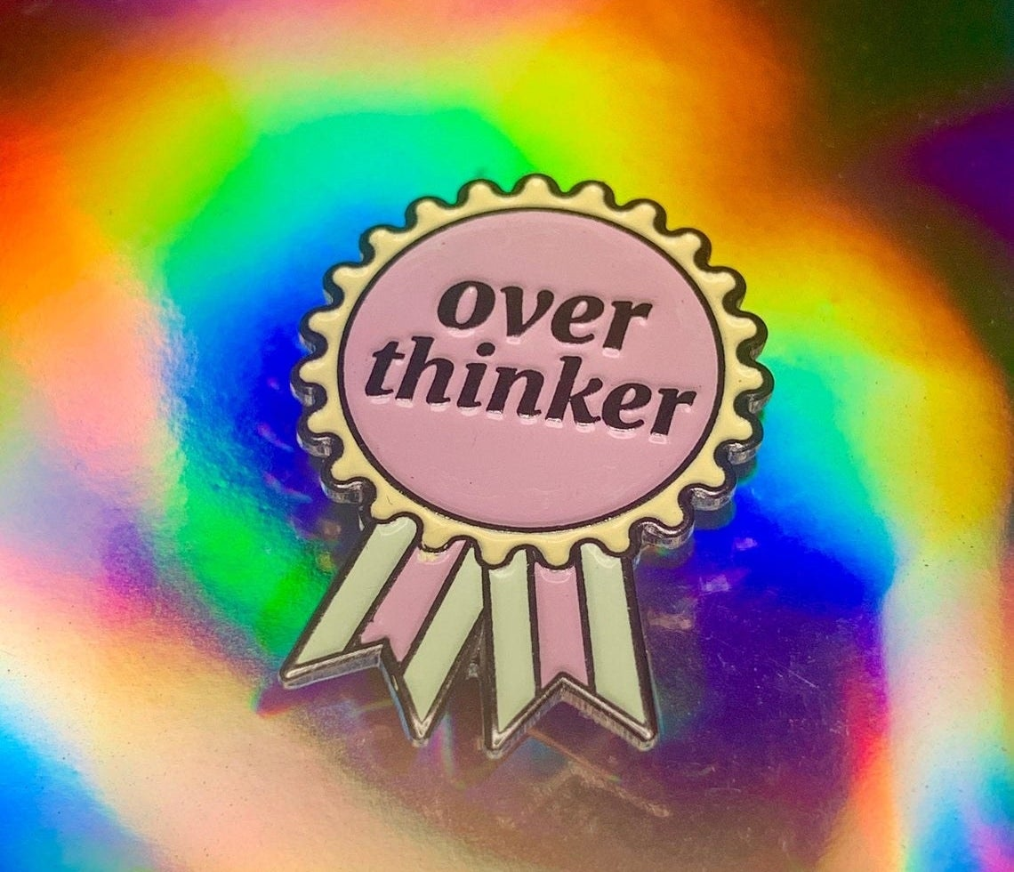 Enamel pin in the shape of a ribbon that says Over Thinker