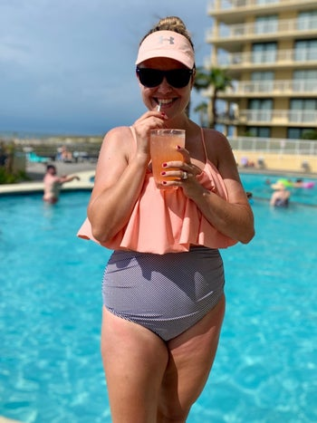 Reviewer wearing the bikini set with peach ruffled top and blue gray striped bottoms