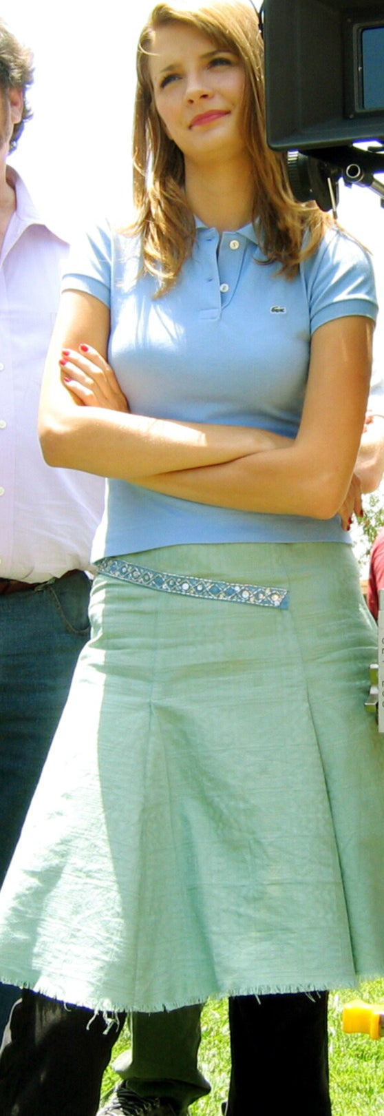Frayed-bottom flared mid-length skirt with pants underneath, sneakers, a half belt that's diagonal and bedazzled, and a Lacoste polo shirt