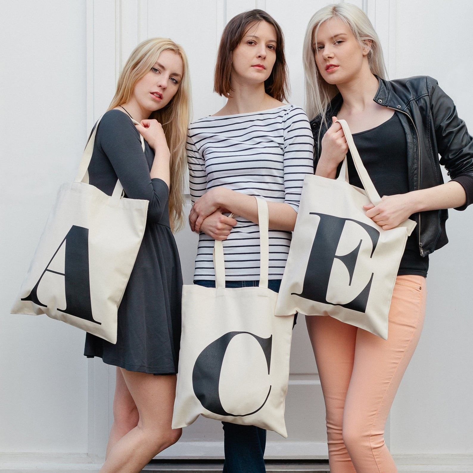 three models each hold a tote bag with a different letter screen printed on it