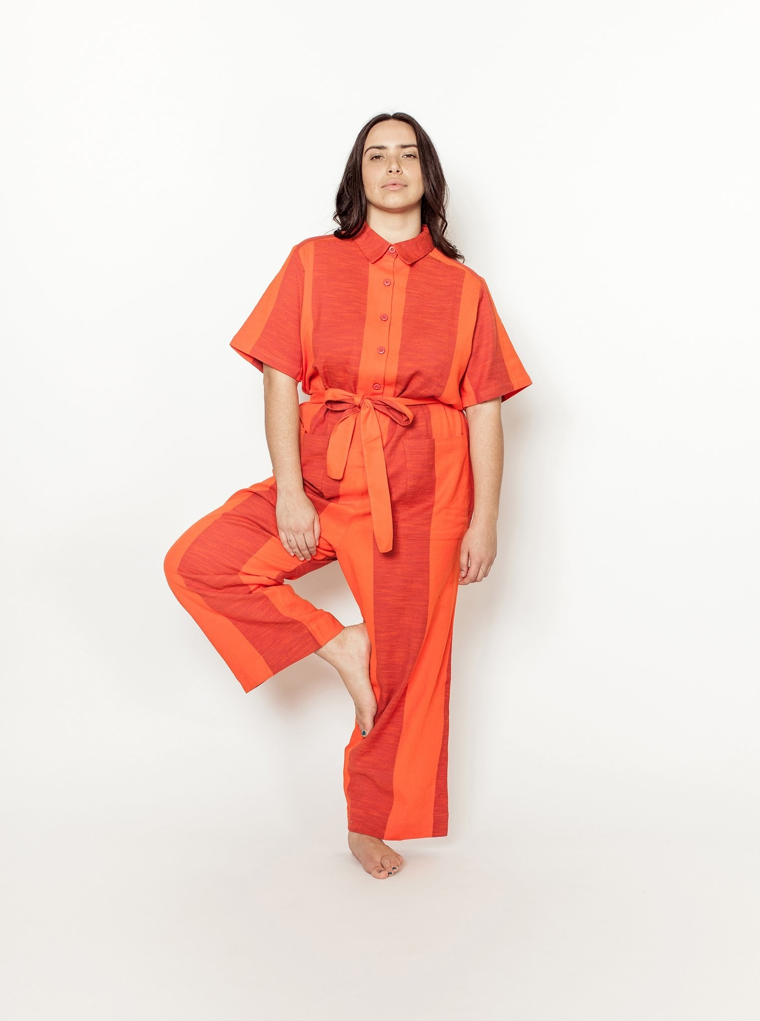 a model wearing the ernie jumpsuit in the tomato textile
