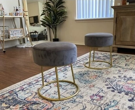 a reviewer's gray velvet stool on an area rug