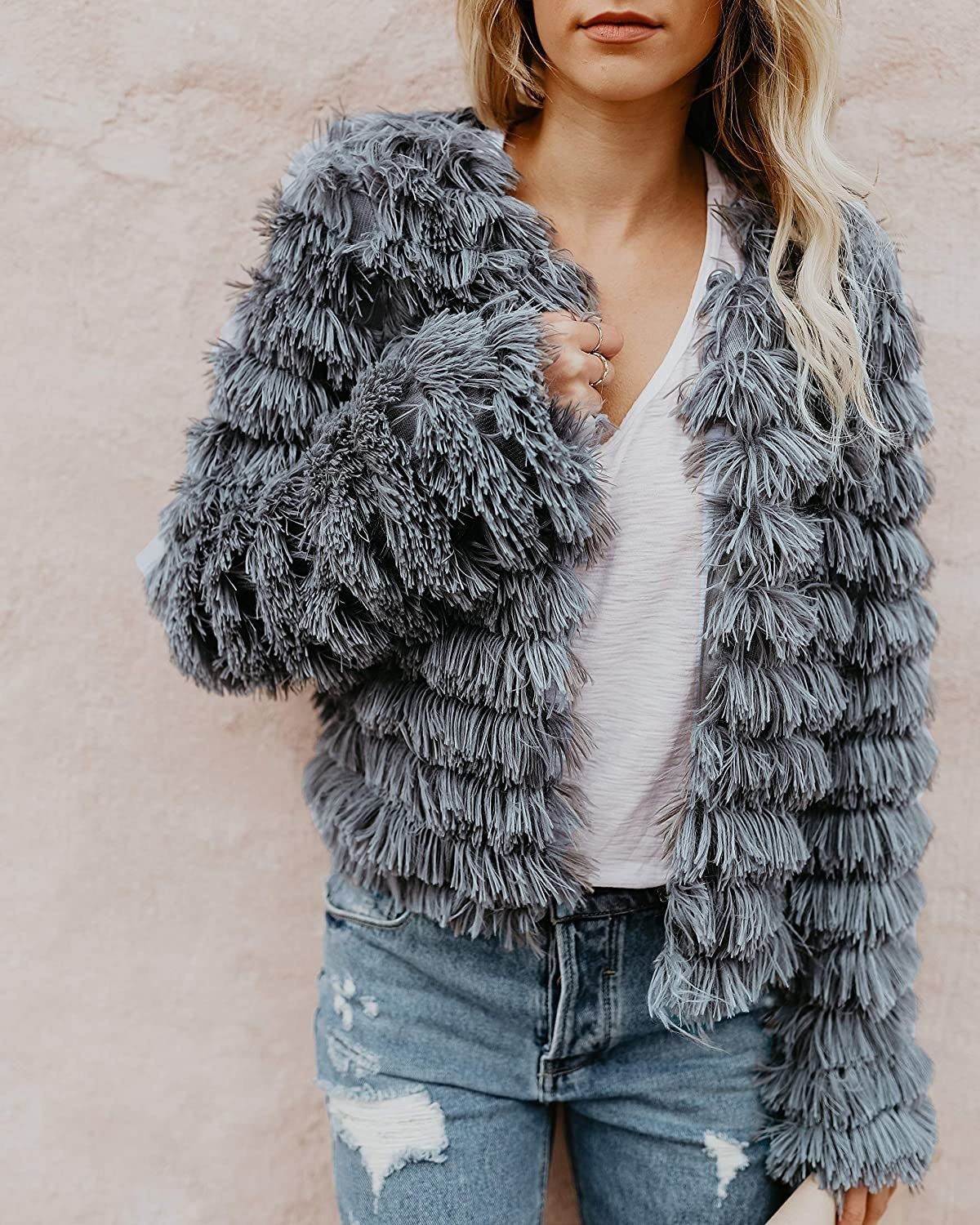 close up of model wearing the gray shaggy parka over a white tee and distressed jeans