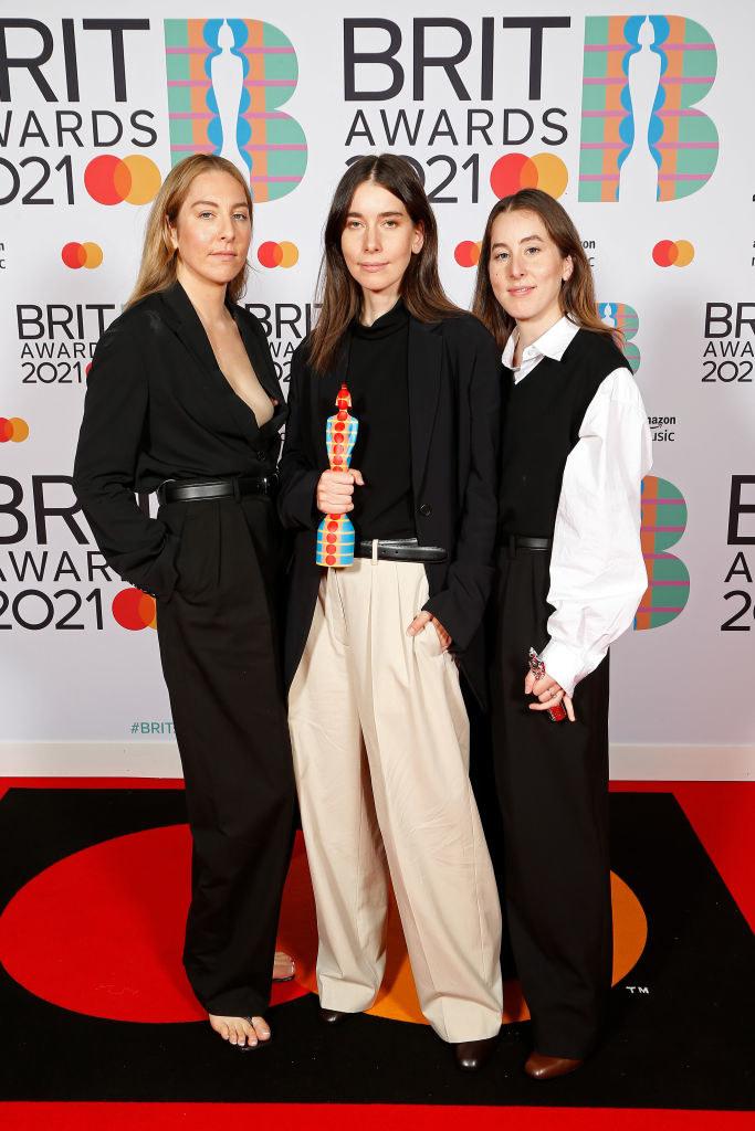 (L-R) Danielle Haim, Este Haim, and Alana Haim of Haim pose in pant suits in the media room with the International Group award