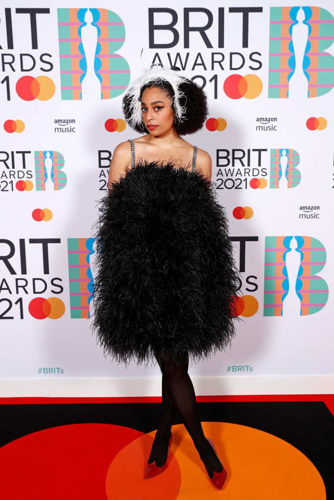 Celeste poses in a short feathered dress and stockings in the media room during The BRIT Awards 2021
