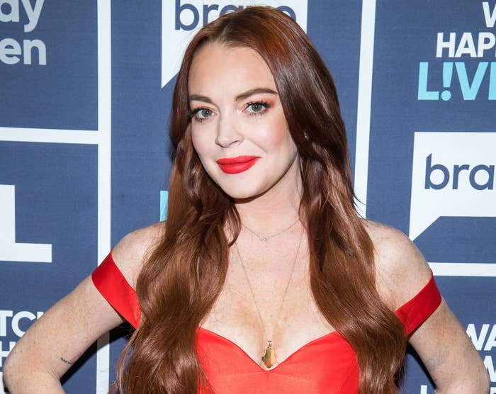 Lindsay wears a red off-the-shoulder dress to an event