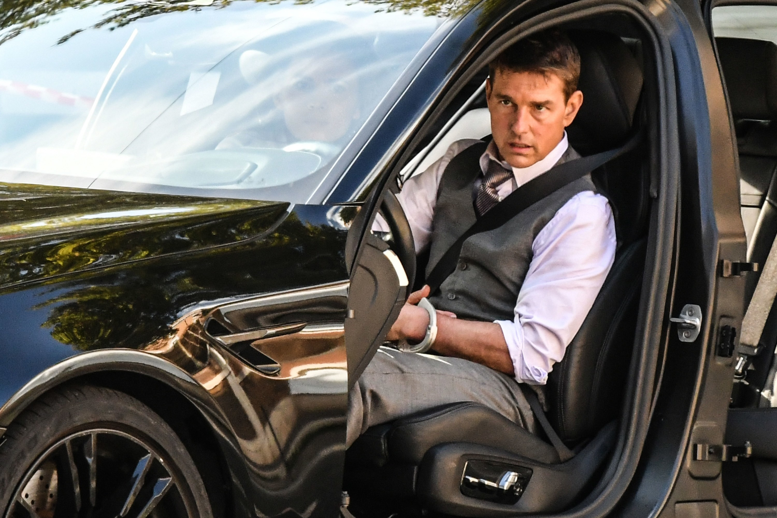 Tom looks serious while driving a car while filming