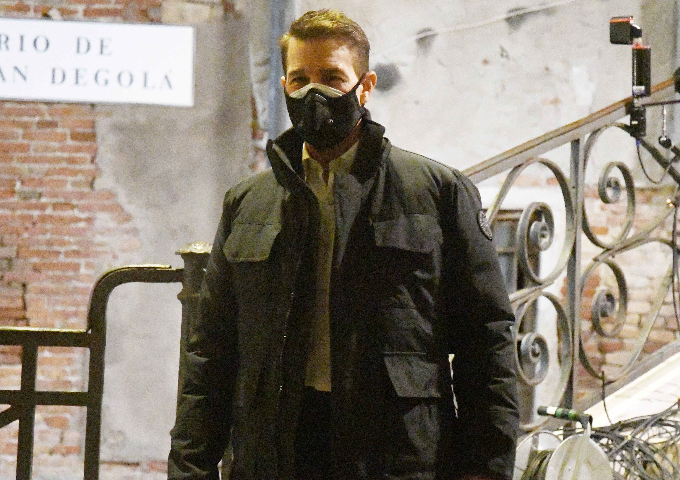 Tom wears a heavy coat and mask while walking around set at night