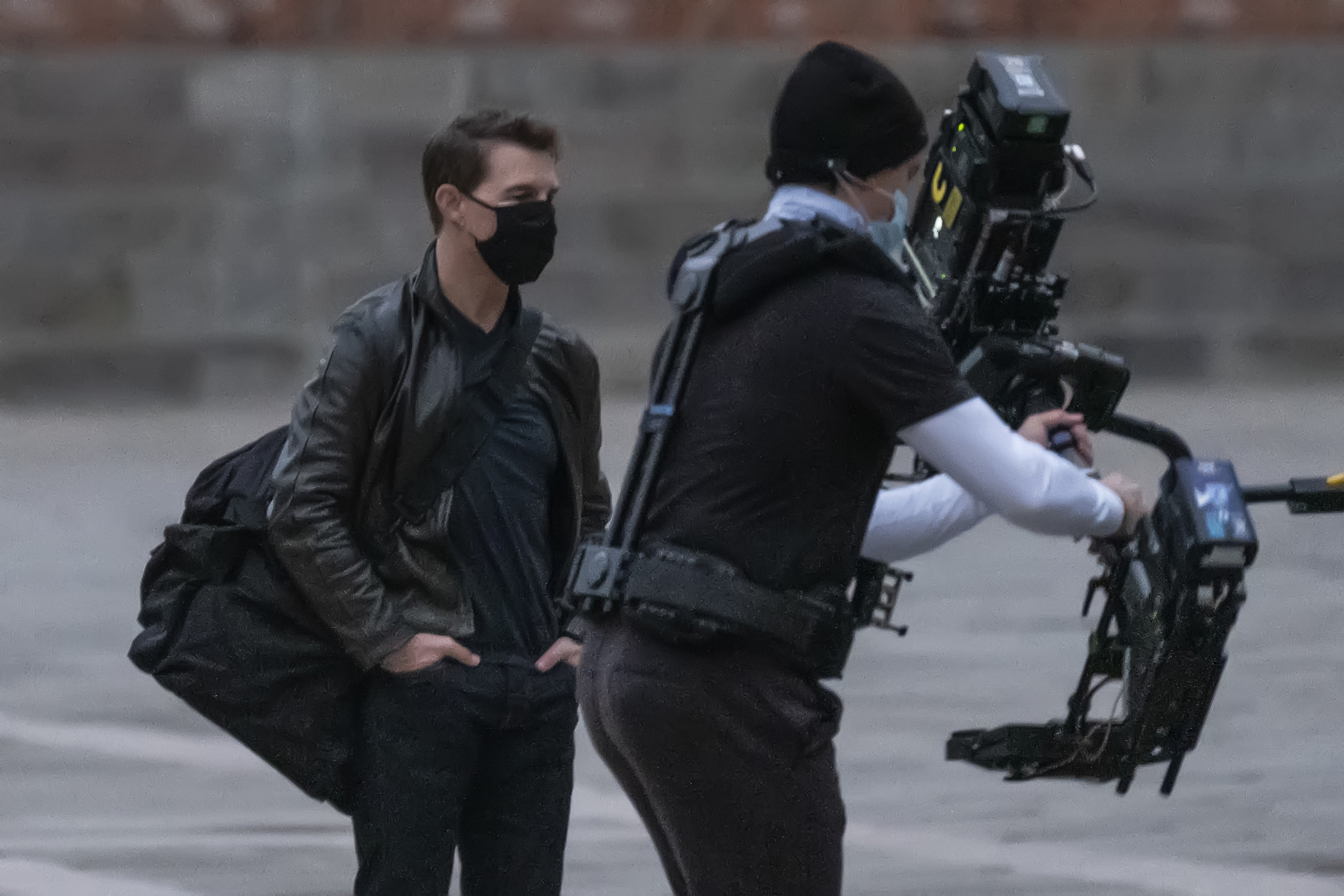 Tom watches a camera operator from a distance while wearing a mask
