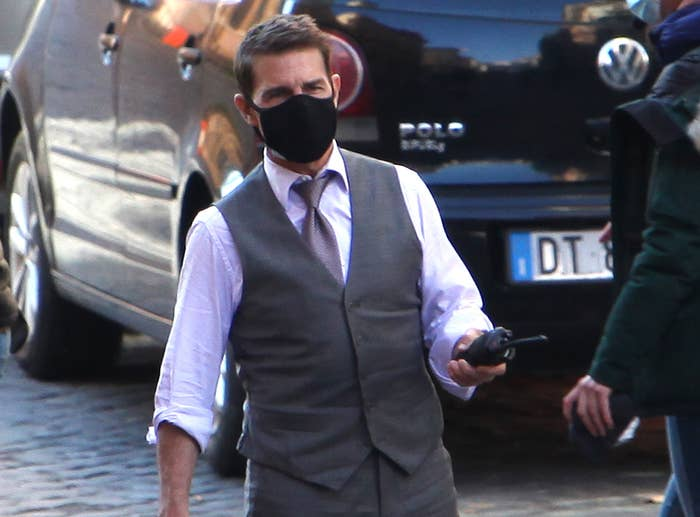 Tom holds a walkie talkie on the set of the movie while wearing a mask