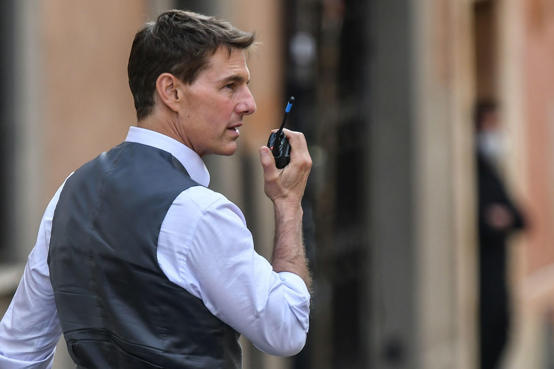 Talk talks into a walkie talkie on set