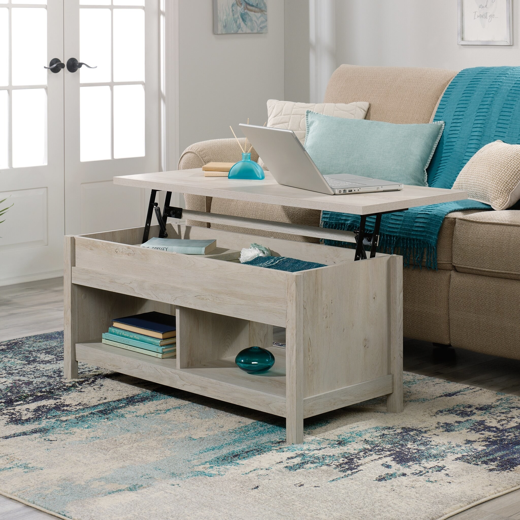 the chalked chestnut coffee table with the top lifted and elevated to show the storage capacity