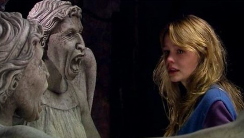 Sally stands in front of two Weeping Angels