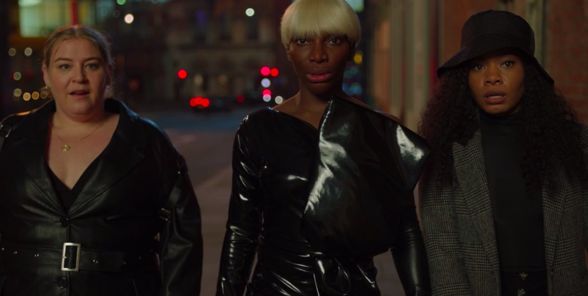 Theodora, Arabella and Terry wear black and walk down the street at night