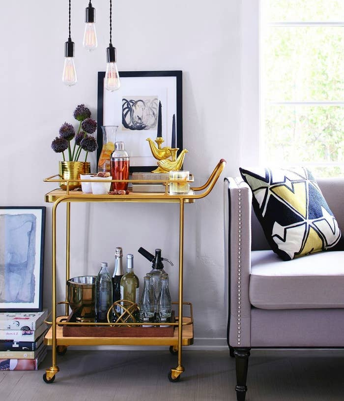 gold and wood bar cart with wheels and bar accessories on top