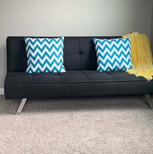 a reviewer's black futon with two throw pillows