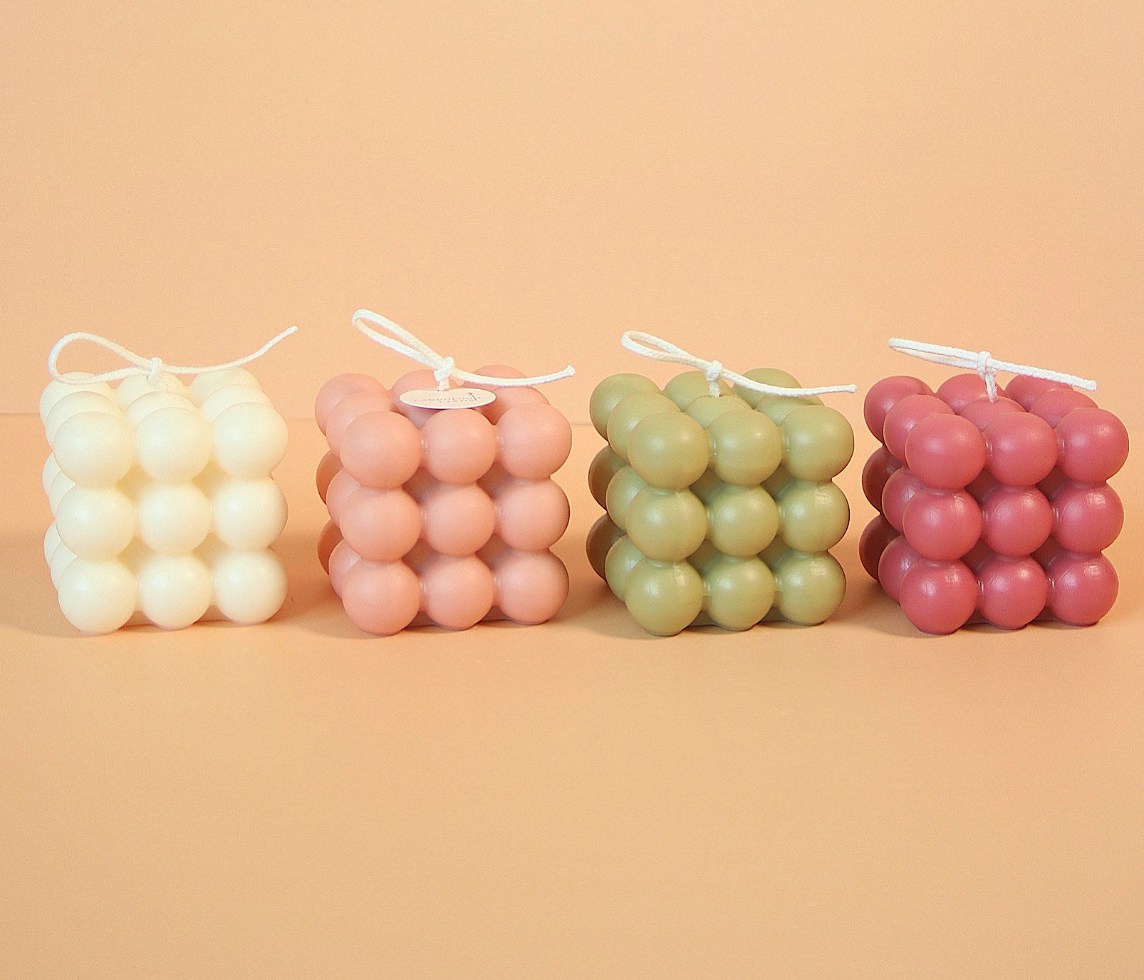 Four square-shaped candles in a row