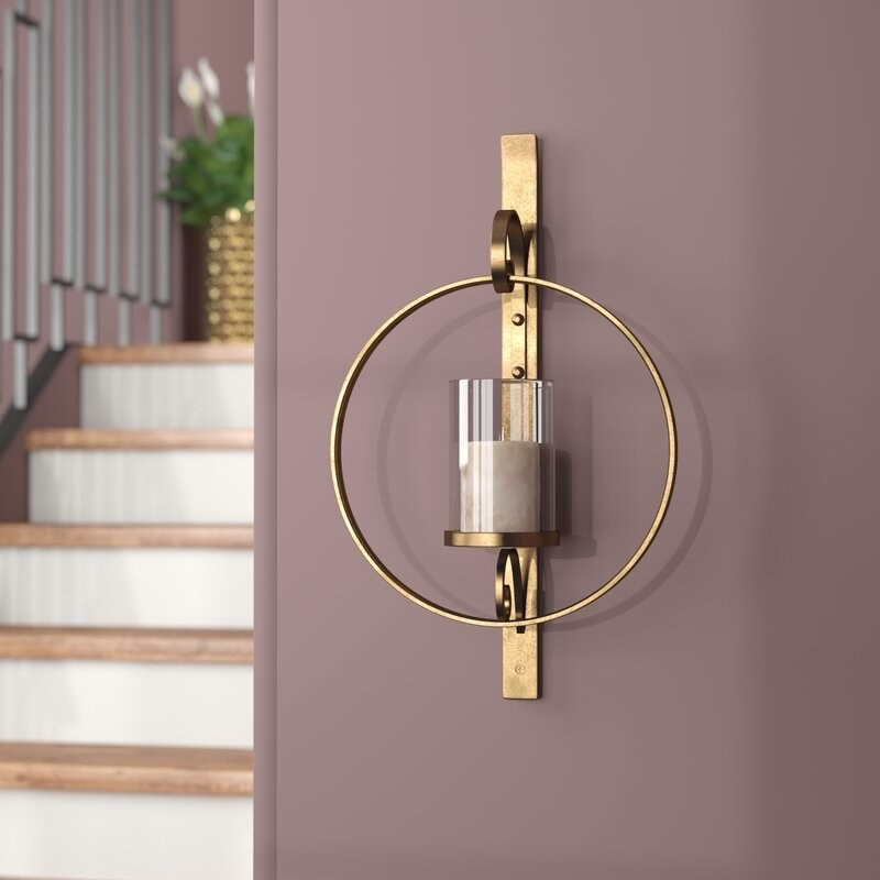 the brass sconce which holds a pillar candle