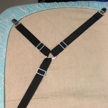 a reviewer image of the black three-sided sheet clips holding a fitted sheet on the underside of a mattress