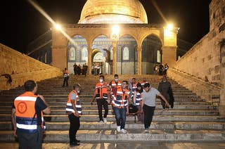Emergency workers in orange vests carrying injured person down steps of a mosque on a stretcher